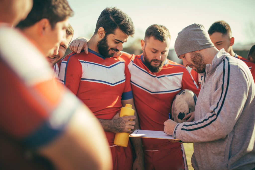 Coach talking to a group of rugby players during time out