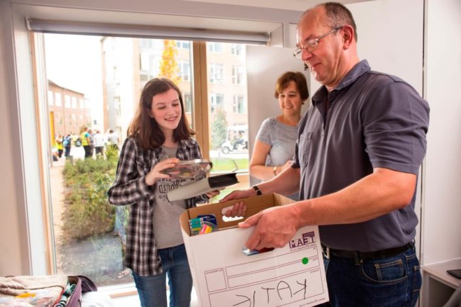 A student and her parents unpack boxes as she moves into a hall of residence.