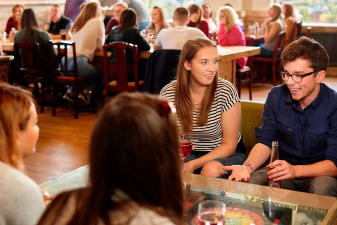 Four students sit round a table and chat over drinks in the SU Bar.