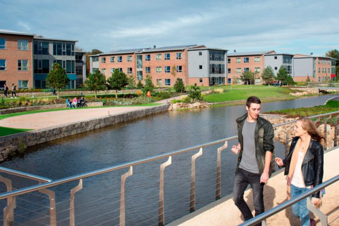 Two students walk across a bridge over a lake near Chancellors Court and Chancellors South halls of residence.