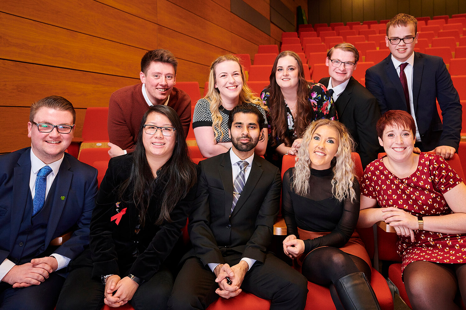 Ten students sit in a lecture theatre while attending a Scholarship Awards Evening to celebrate their success.