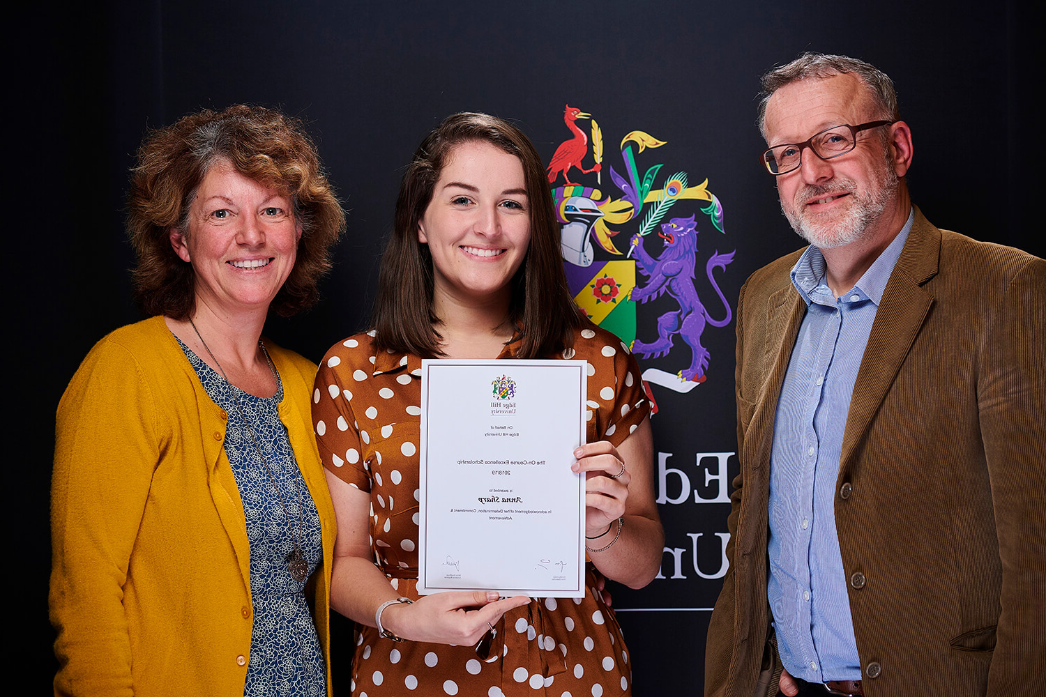 Scholarship winner Anna Sharp, with her family, shows off her certificate while attending a Scholarship Awards Evening.